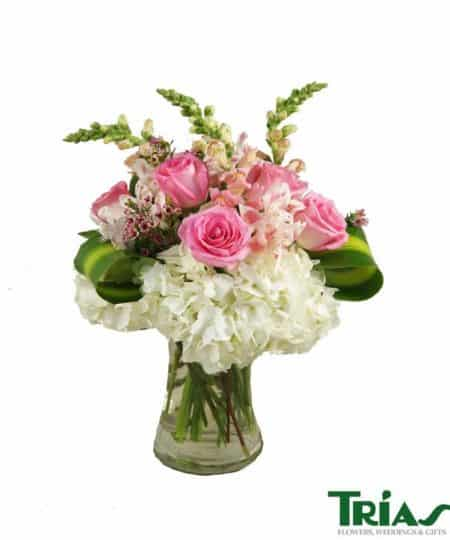 A gorgeous and unique arrangement of white hydrangeas, pink roses, pink snapdragons, pink alstromerias, pink wax flowers and masangena leaves in a beautiful clear hourglass vase.